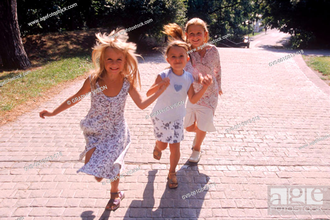 Stock Photo: Three girls running in a park.