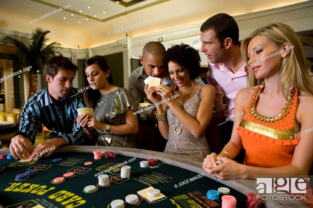 Stock Photo: Young men and women gambling at poker table in casino, smiling.