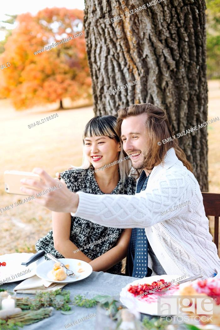 Stock Photo: Couple taking selfie at outdoor table.