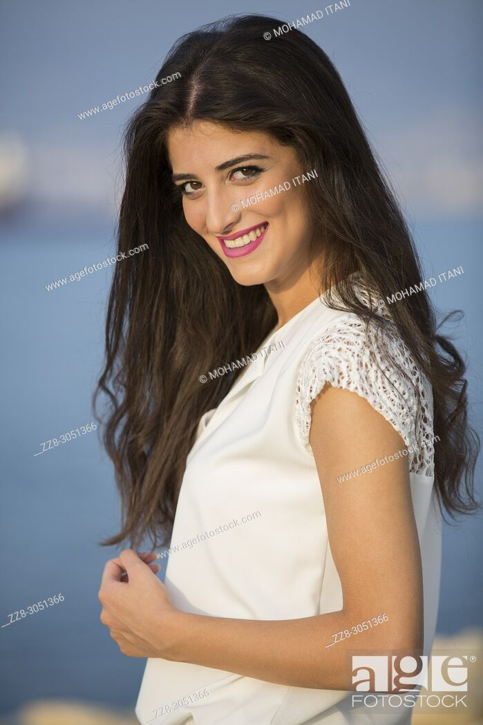 Stock Photo: Portrait of a beautiful young woman smiling outdoors.