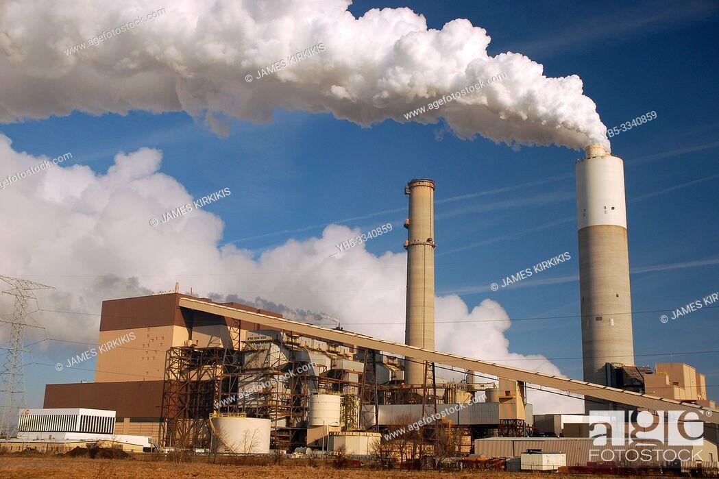 Stock Photo: A smoke stack belches smog into a blue sky.