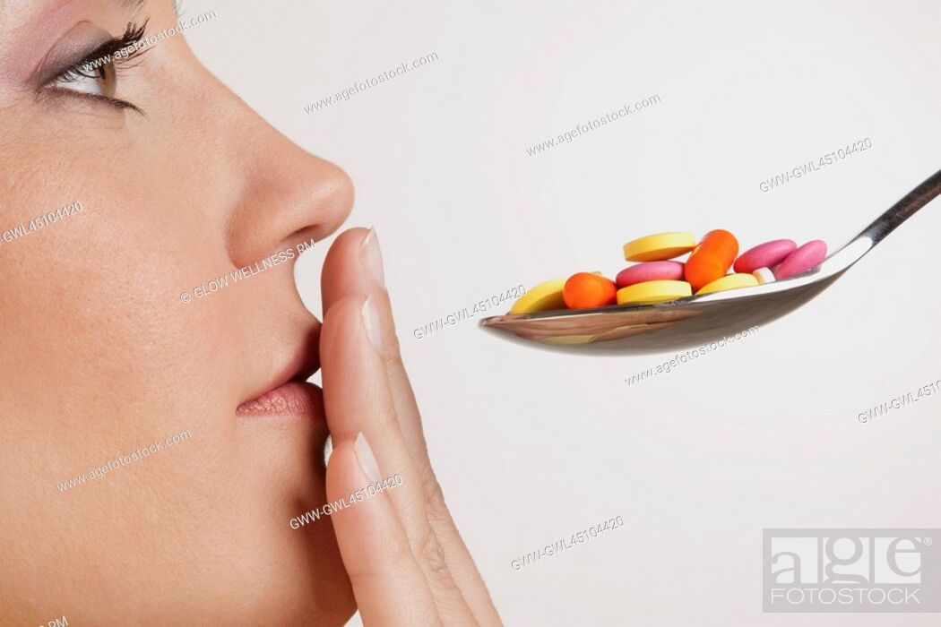 Imagen: Close-up of a woman with a spoonful of pills.