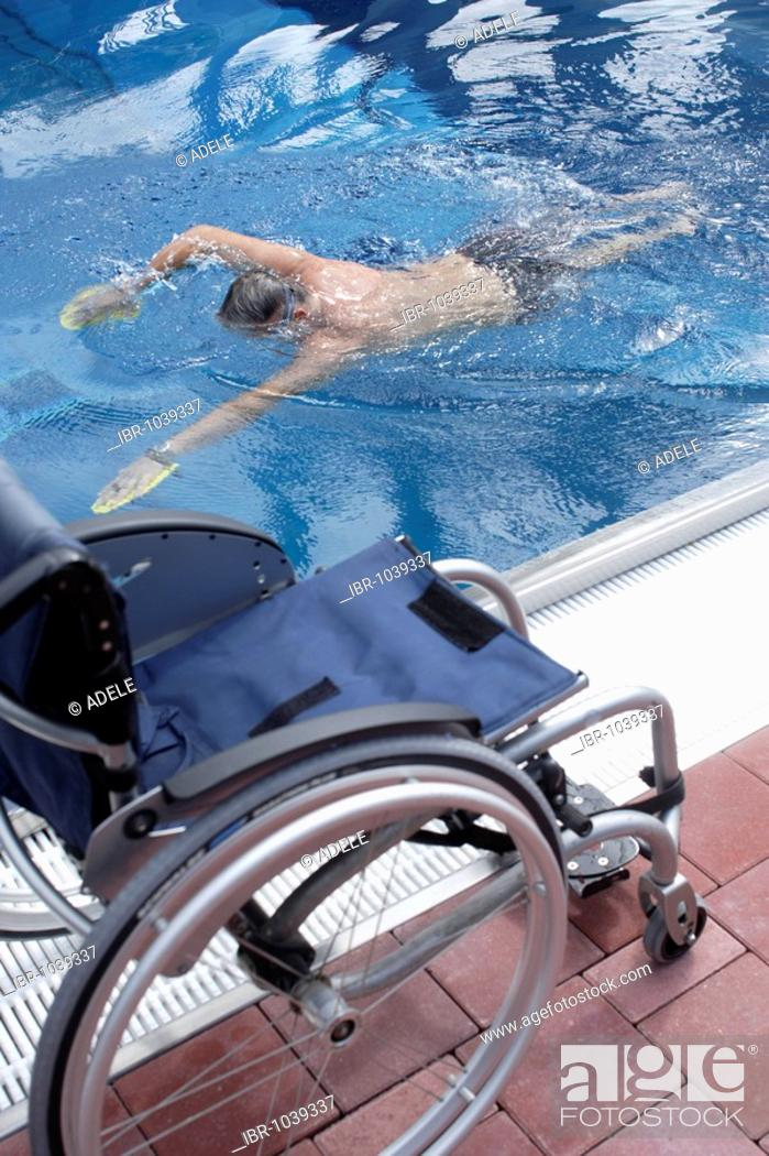 Young, handicapped man, wheelchair user, swimming exercises in a ...