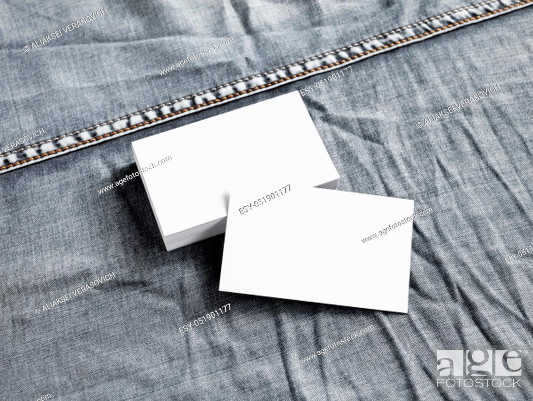 Stock Photo: Blank white paper business cards on gray denim background.