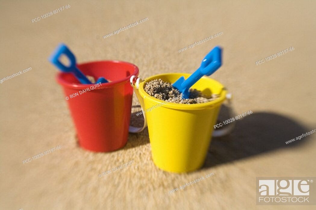 Stock Photo: Two sets of brightly colored shovel and pails on a sandy beach.