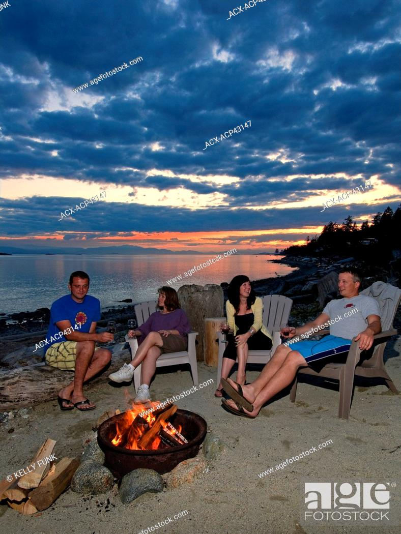 Stock Photo: After a beautiful summer day, friends relax around the fire near Sechelt, British Columbia, Sunshine coast, Vancouver coast and mountain region, Canada.