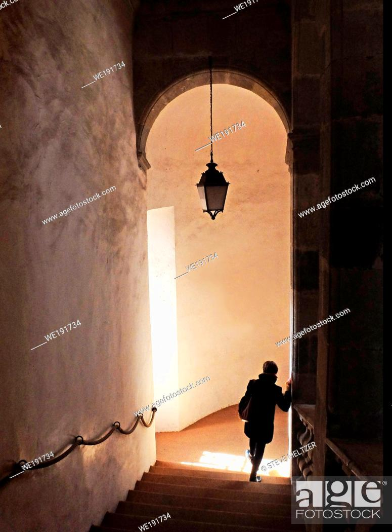 Stock Photo: A woman descends th long, Baroque era staircase in the Musee de Faïence, Narbonne, France.