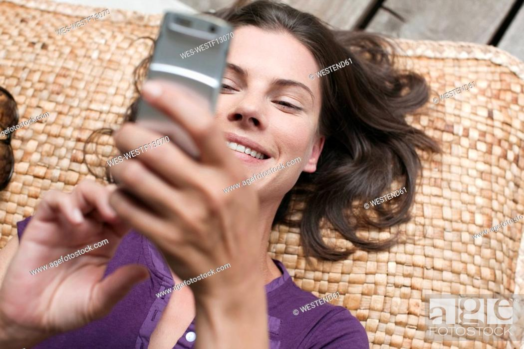 Stock Photo: Germany, Hamburg, Woman lying on terrace, using mobile phone, elevated view.