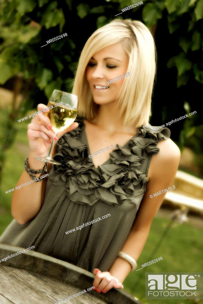 Imagen: beautiful young woman with glass of wine standing at wine cask.