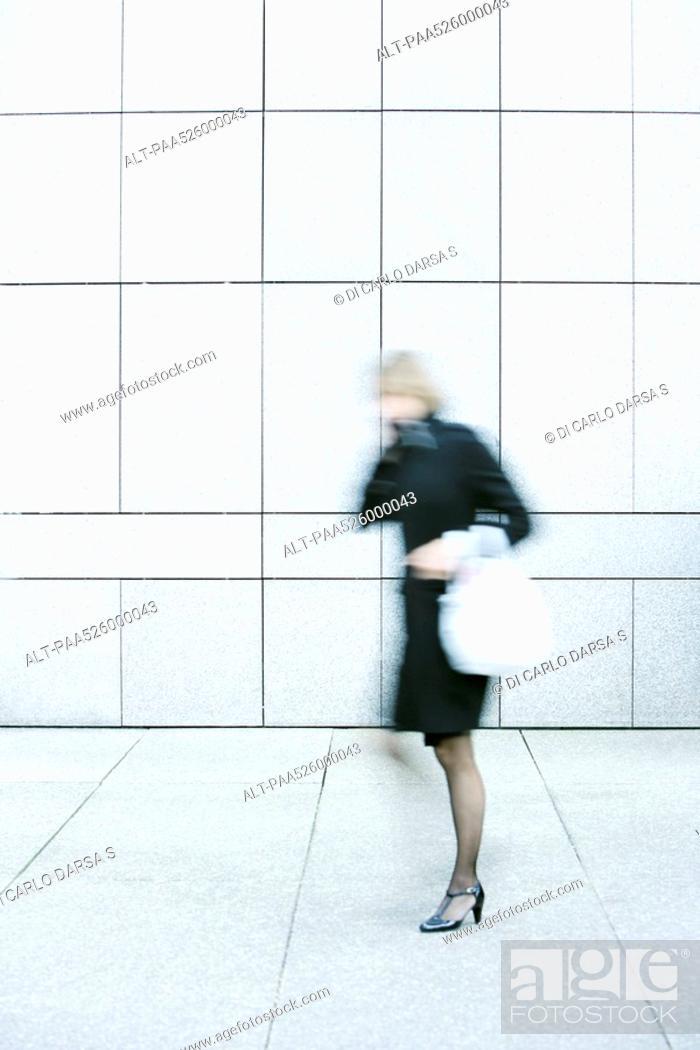 Stock Photo: Businesswoman talking on phone while walking down sidewalk.