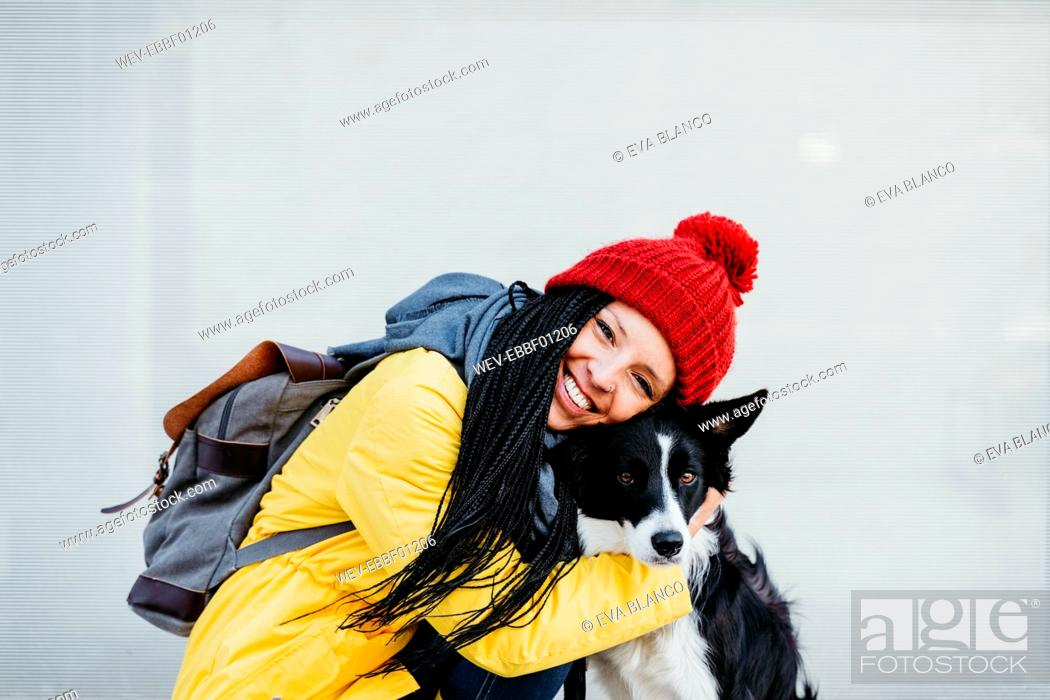 Stock Photo: Happy woman embracing pet dog against wall.