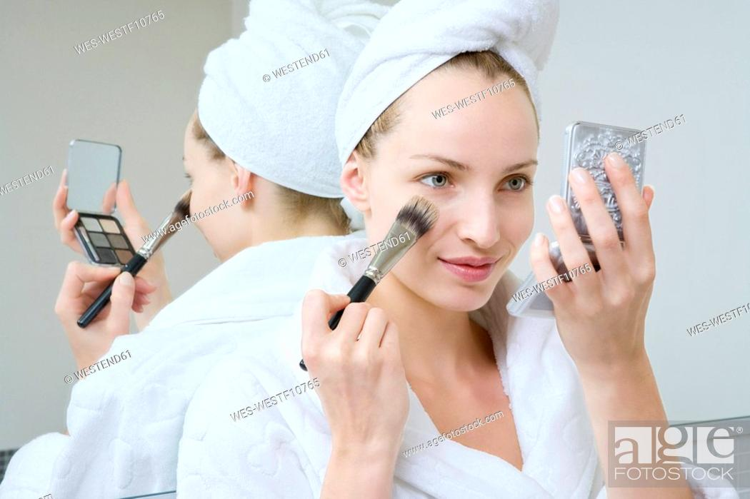 Stock Photo: Young woman using make-up brush, portrait.