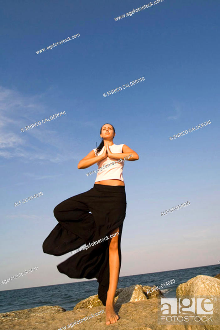 Stock Photo: Young woman doing yoga exercises on rock.