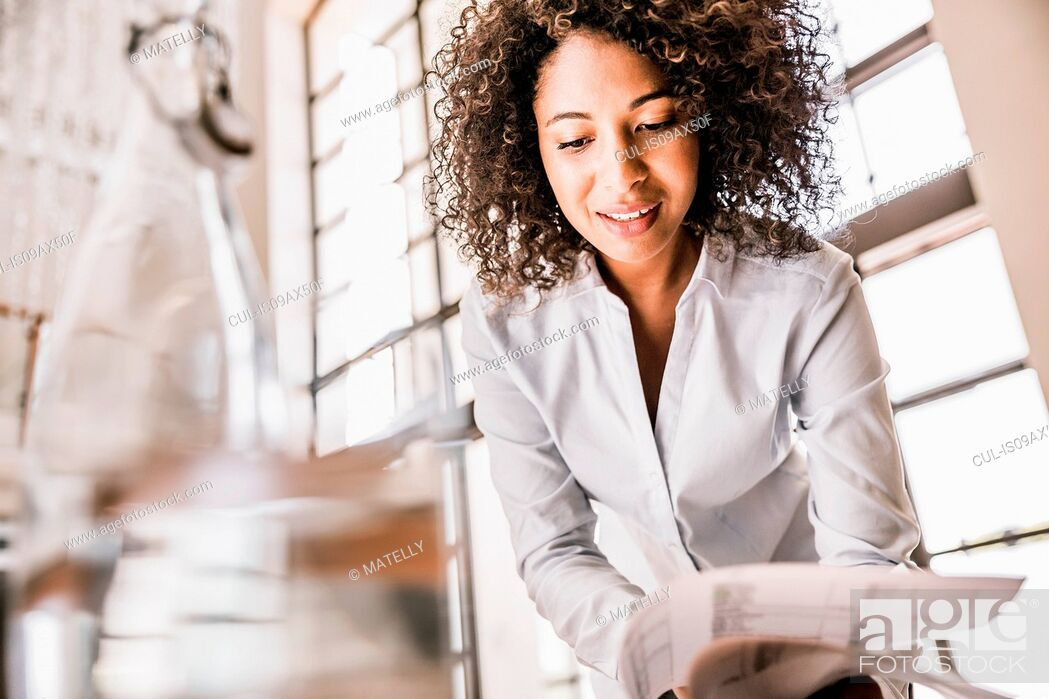 Stock Photo: Curly haired business woman looking down at paperwork smiling.