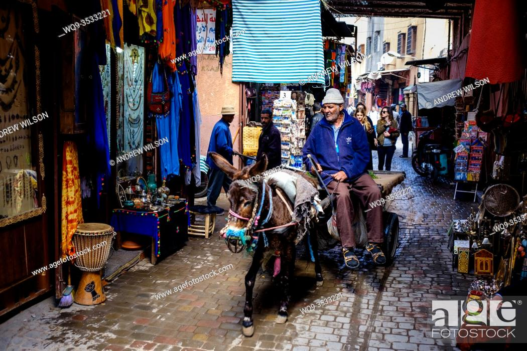Stock Photo: A man riding a donkey and cart through the medina in Marrakech, Morocco, North Africa.