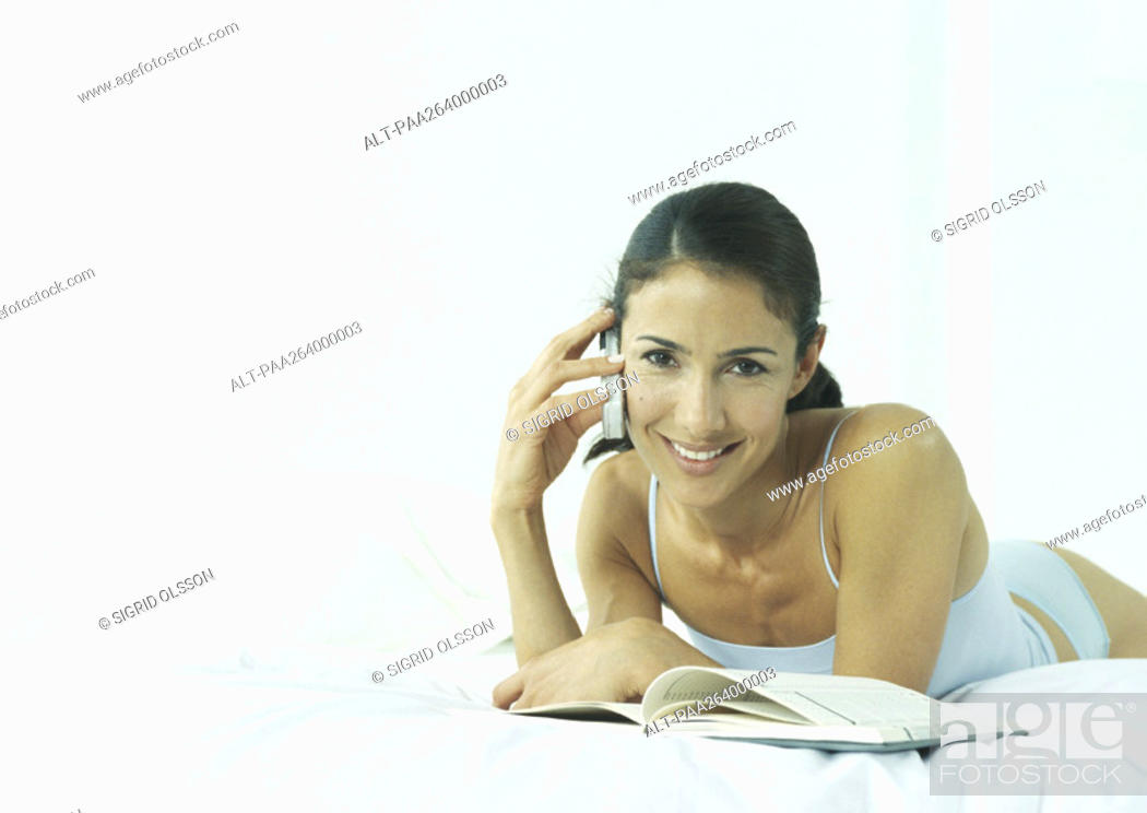 Stock Photo: Young woman lying on stomach in underclothes holding cell phone to ear, smiling at camera.