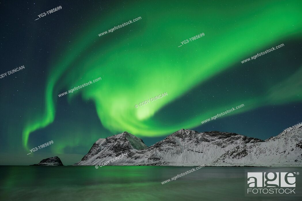 Stock Photo: Aurora Borealis - Northern Lights shine in sky over snow covered mountains from Vik beach, Vestvågøy, Lofoten Islands, Norway.