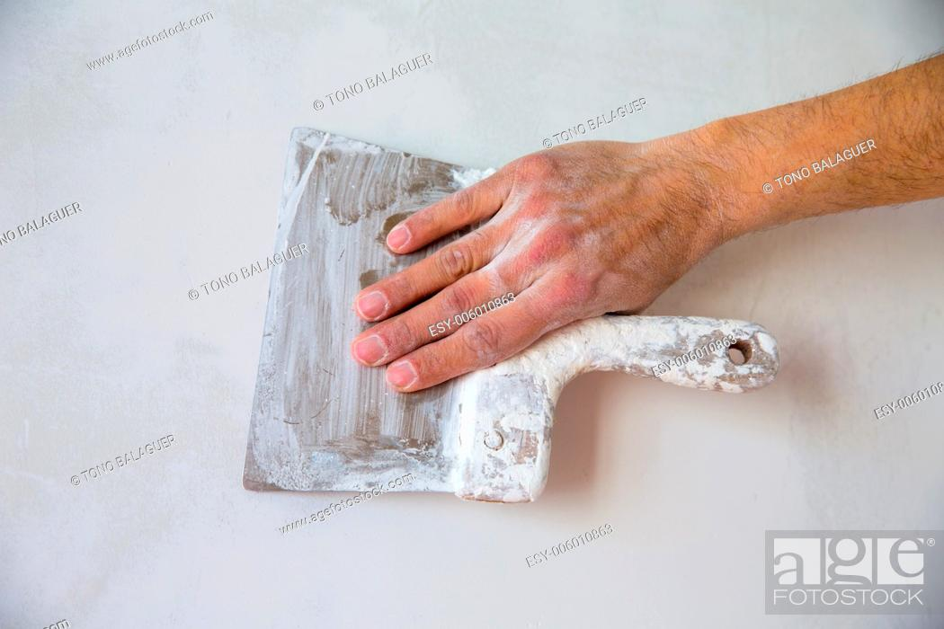 Stock Photo: Plastering man hand with plaste and plaster spatula trowel in wall.