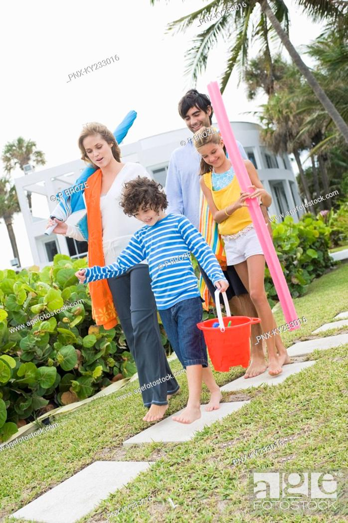 Stock Photo: Family walking in the garden of a tourist resort.