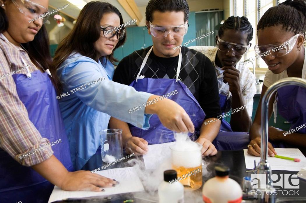 Stock Photo: Students and teacher performing experiment in chemistry lab.