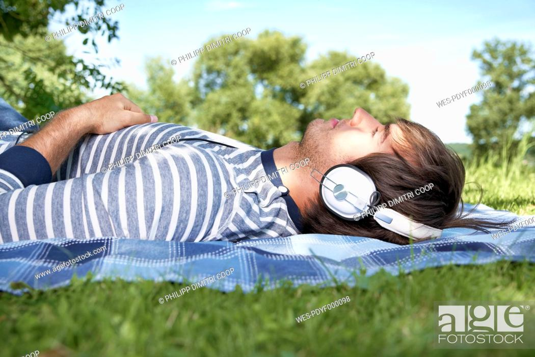 Stock Photo: Germany, Cologne, Young man listening music in meadow.