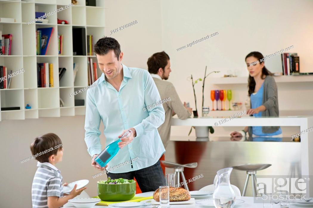 Stock Photo: Man and son setting table for lunch.