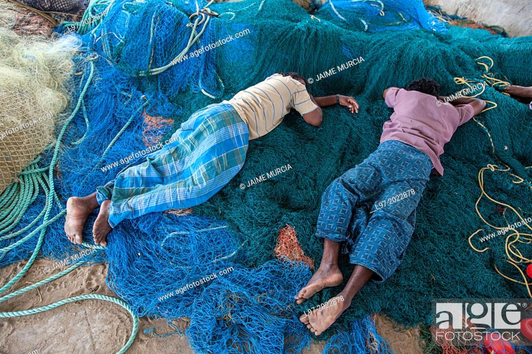 Stock Photo: Fishermen sleep on their nets after returning from fishing in the Bay of Bengal, Tamil Nadu state, South India.