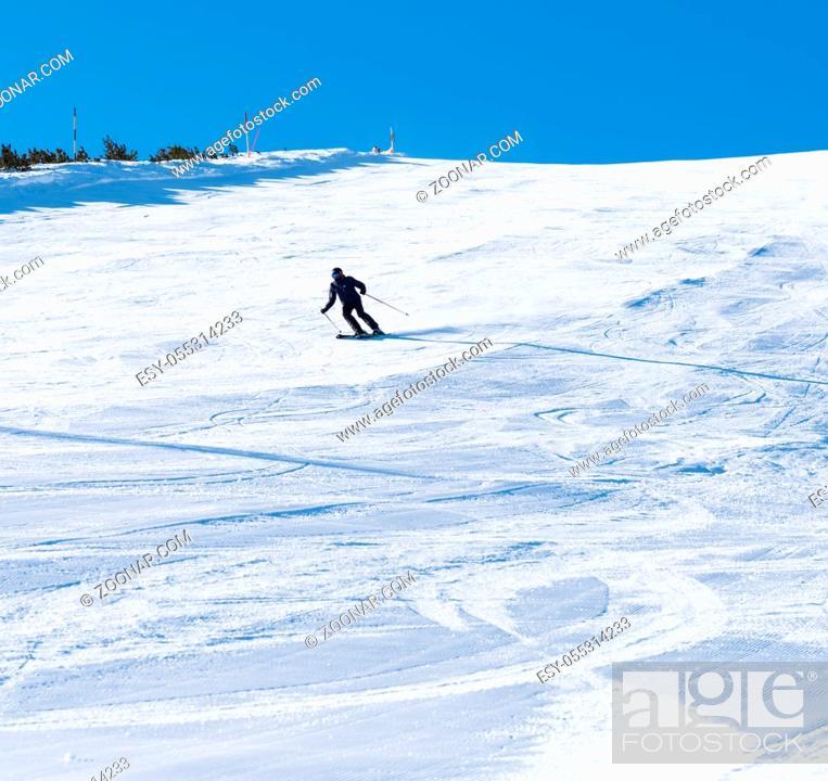 Photo de stock: Bulgaria. Bansko. 10 February 2020. Skier riding down the huge snowfield splashing powder snow.