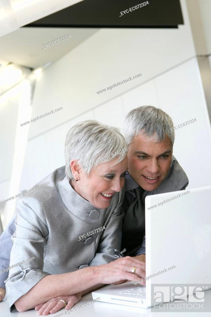 Stock Photo: Happy mature couple looking at laptop in airport.