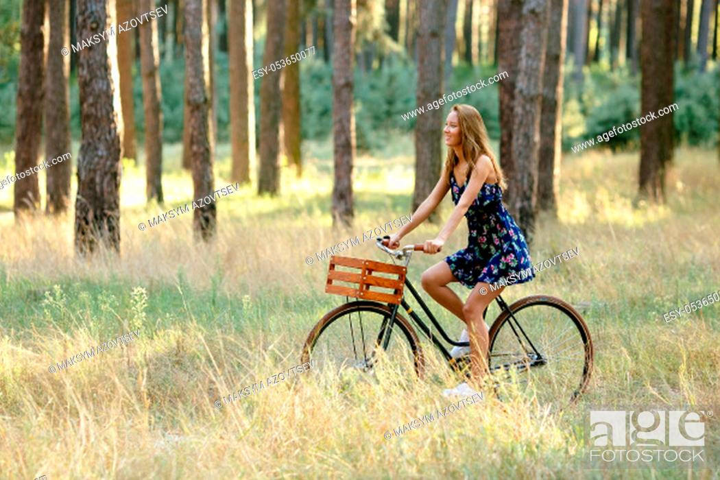 Stock Photo: Girl rides a bicycle with a basket in the woods.