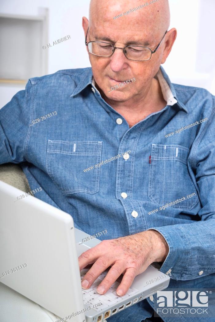 Stock Photo: Senior man using a laptop computer at home.