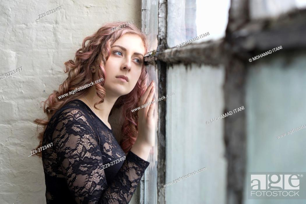 Stock Photo: Sad woman standing by the window.