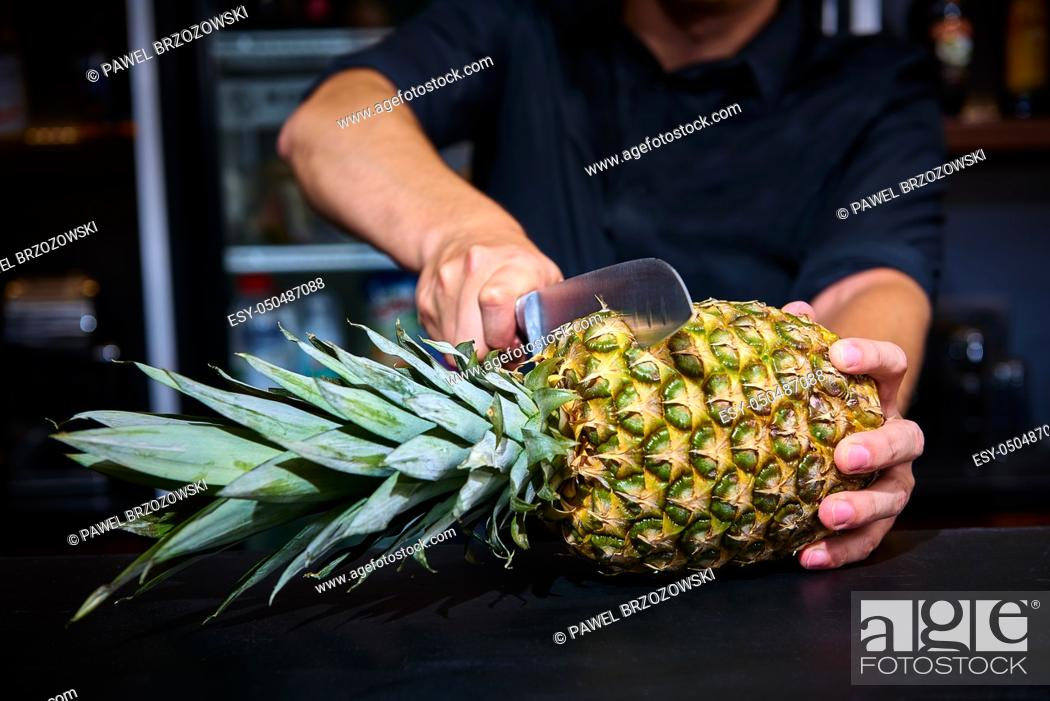 Stock Photo: Barkeepr cutting pineapple on the counter bar in a pub with blurry background.