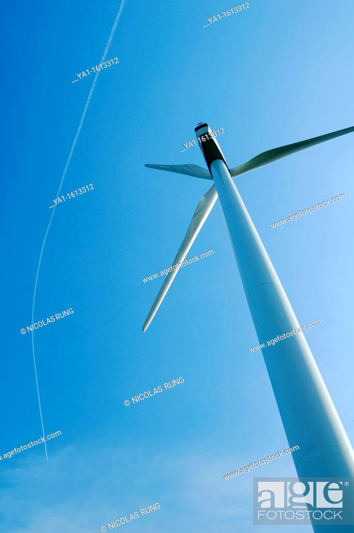 Stock Photo: Wind turbine with a smoke trace of airliner jet plane on blue sky, Lorraine region - France.