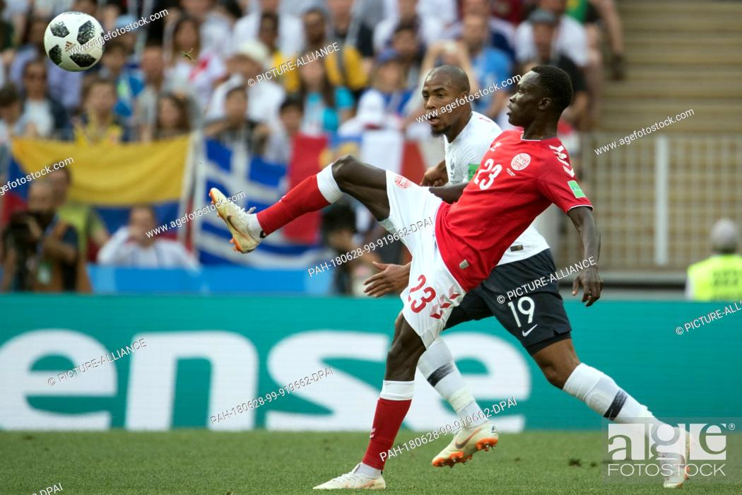 Stock Photo: 26 June 2018, Russia, Moscow, Soccer, FIFA World Cup 2018, Group C, Matchday 3 of 3 at Luzshniki Stadium: Pione Sisto (L) from Denmark and Djibril Sidibe (R).