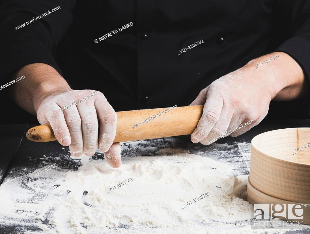 Imagen: wooden rolling pin in men's hands, white wheat flour is poured on the table.