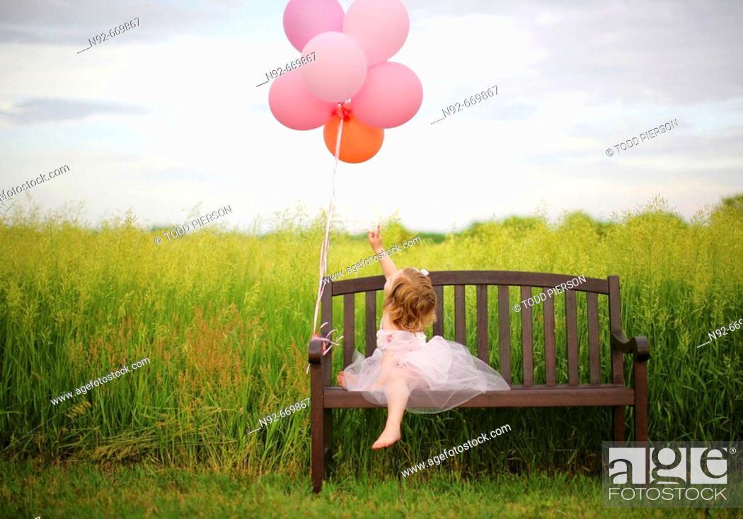 Stock Photo: Girl, age 3 looking at balloons. In Illinois at farm. Hay feild.