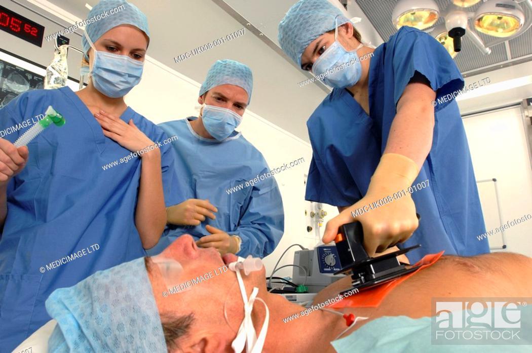 Stock Photo: Doctors using a defibrillator to resuscitate a male heart attack victim.