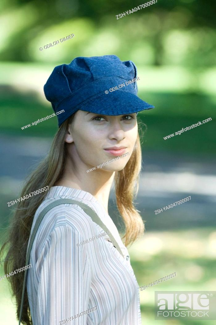 Stock Photo: Young woman in park, wearing cap, portrait.