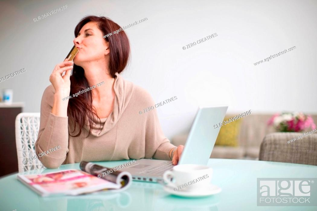 Stock Photo: Woman paying her bills at home.