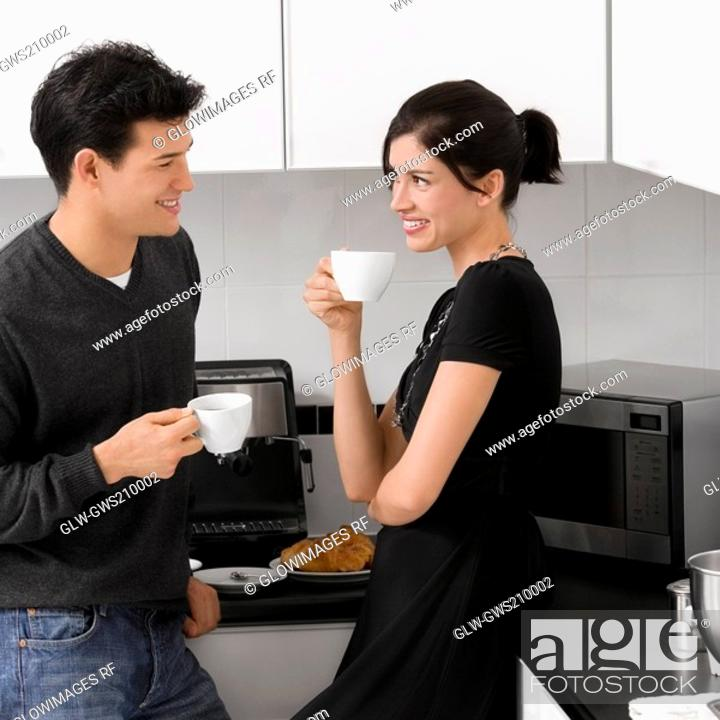 Stock Photo: Young couple holding their coffee cups in the kitchen and smiling.