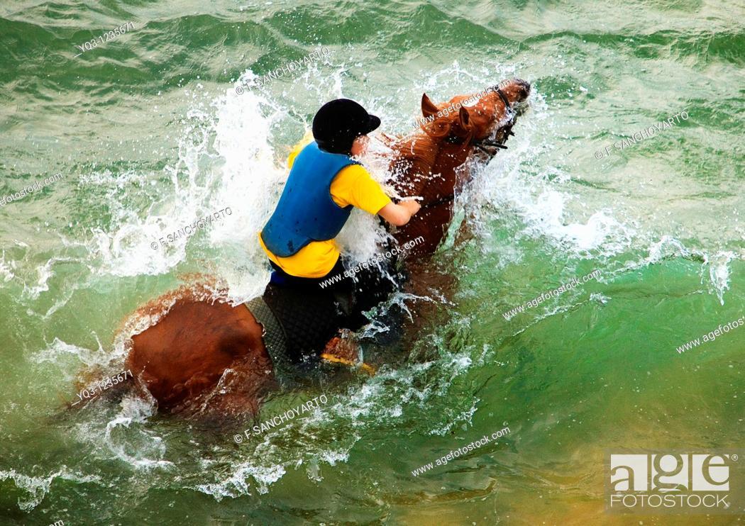 Stock Photo: A caballo sobre las olas en la playa de Oriñón, Castro Urdiales, Cantabria.