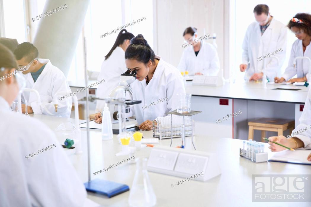Stock Photo: College students using microscope conducting scientific experiment in laboratory.