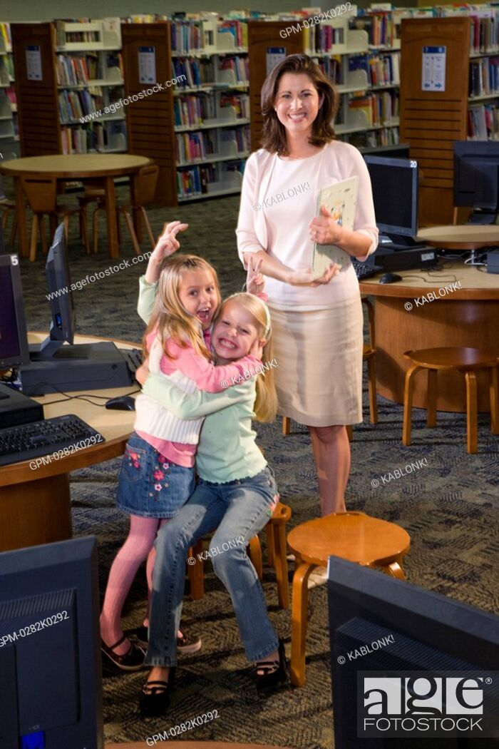 Imagen: Portrait of young woman with girls embracing in library.