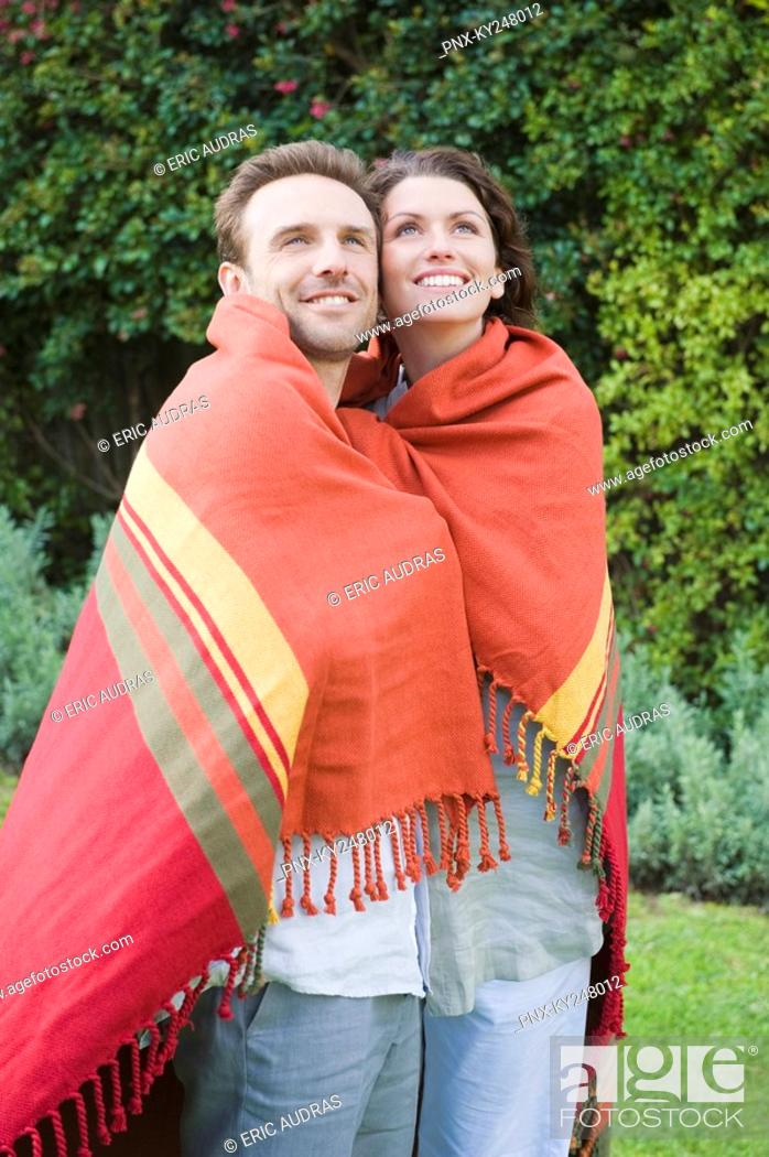Stock Photo: Couple wrapped in a shawl and smiling.