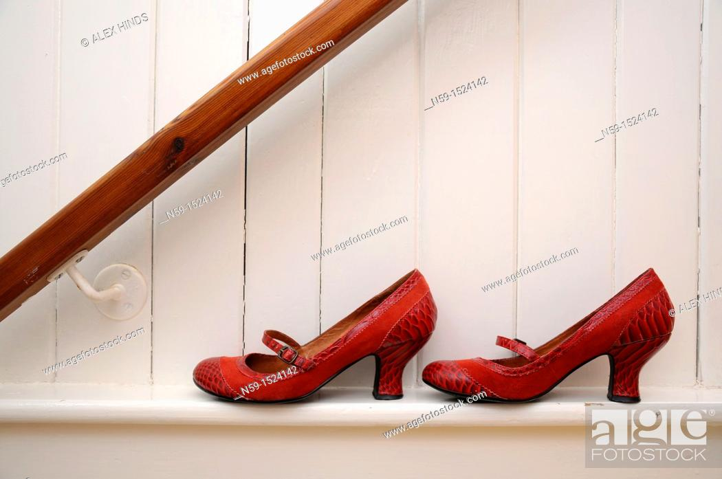 Stock Photo: Red shoes on white wall.