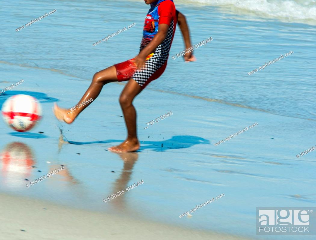 Stock Photo: A young African lad dressed in a sun-protective bathing suit, kicks a ball on the beach at low tide. Cape Town South Africa.