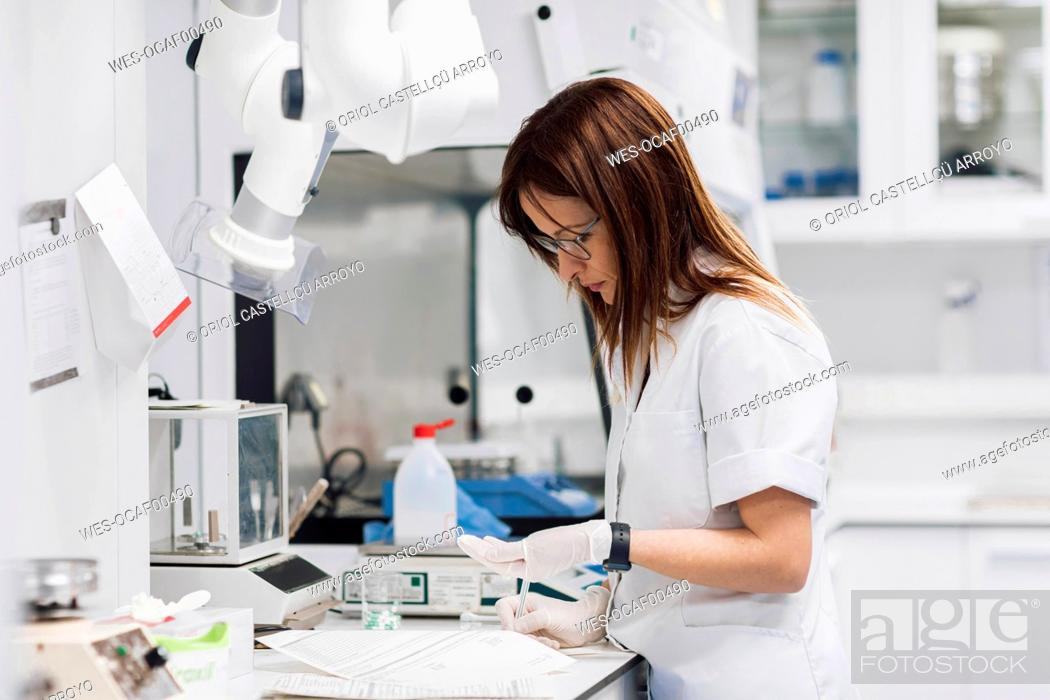 Stock Photo: Mature female pharmaceutical technician holding pills while standing by desk at laboratory.