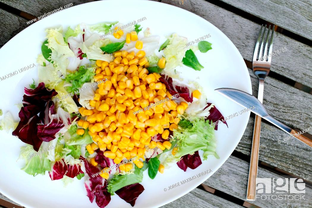Stock Photo: Salad with lettuce and corn on wooden table.