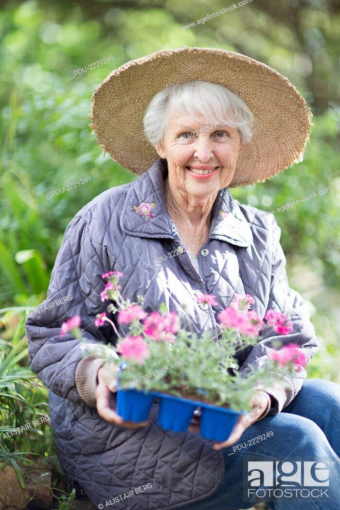 Stock Photo: Portrait of senior woman, aged 77, in her garden.